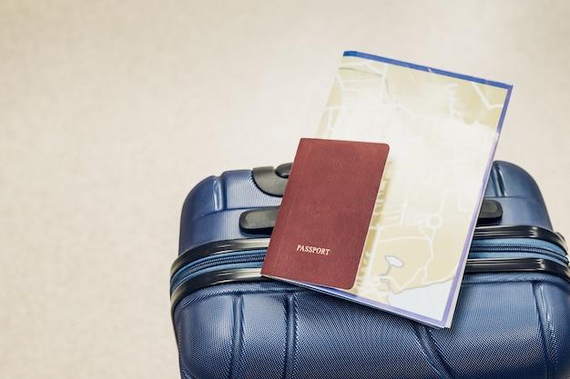 空港、旅行の休暇のコンセプトで青いスーツケースにパスポートと地図のレイアウトを閉じます