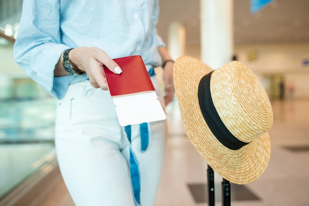 Close-up of passports and boarding pass in female hands at airport