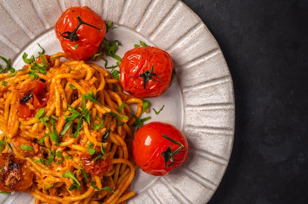 Close up pasta with baked cherry tomatoes, cheese and parsley on a dark textured background