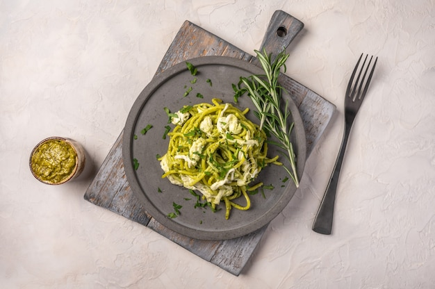 Close up pasta with pesto, stracciatella cheese and parsley served on gray ceramic plate with fork