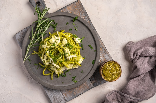 Close up pasta with pesto, stracciatella cheese and parsley served on gray ceramic plate on wood
