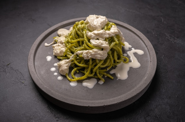 Close up pasta with pesto, stracciatella cheese served on gray ceramic plate on dark grafit background, selective focus
