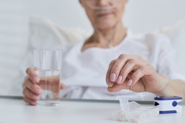 Close-up of patient holding glass of water and taking pills at hospital
