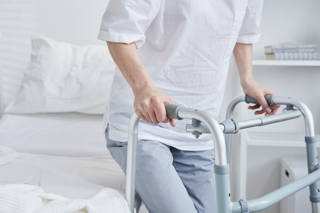 Close-up of patient standing up with the walker from the hospital bed