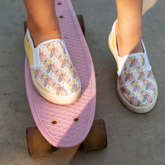Close-up of patterned shoes and pink skateboard