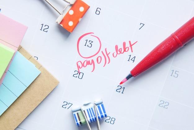 Close up of pay debt word on calendar