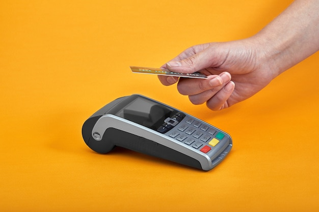 Close-up of payment machine buttons with human hand holding plastic card
