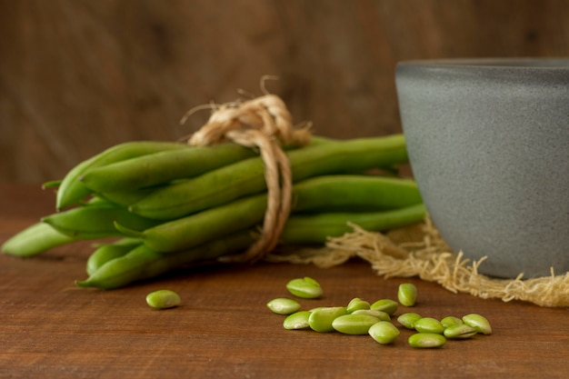 ボウルとテーブルの上のクローズアップのエンドウ豆の鞘