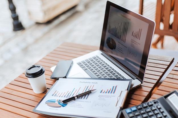 Крупным планом ручка и финансовая диаграмма на столе в кафе