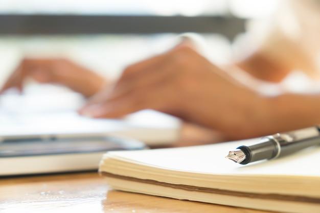 Close up penna e sfocatura bokeh mani di lavoro di imprenditrice asiatica