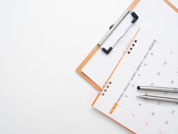 テーブルトップビューの隔離されたコピースペースのドキュメントボードでカレンダーのペンを閉じる