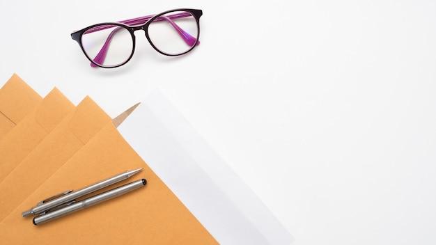 ドキュメント封筒のペンとテーブルトップビューのコピースペースのメガネをクローズアップ