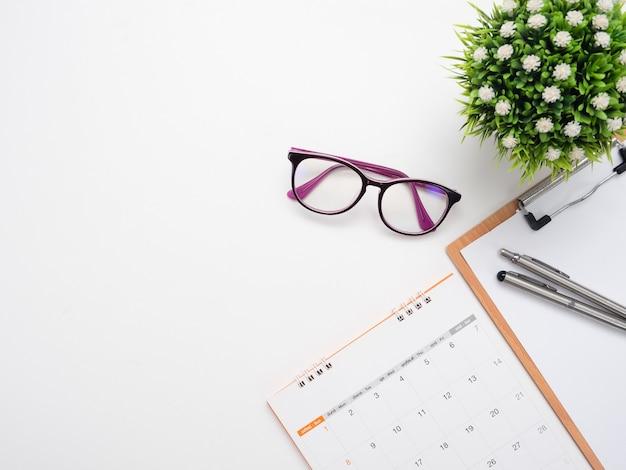 ドキュメントのpoardとメガネのカレンダーの上面図のコピースペースにペンを閉じる Premium写真