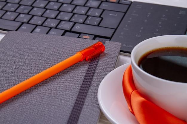 一杯のコーヒーとpcキーボードのクローズアップペン。