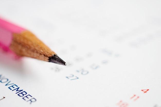 カレンダーページの鉛筆を閉じて、日付計画の概念をマークします