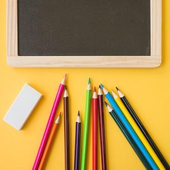 Крупным планом карандаши и резины возле доски