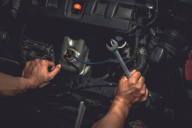 Close up, people are repair a car use hand a wrench and a screwdriver to work.