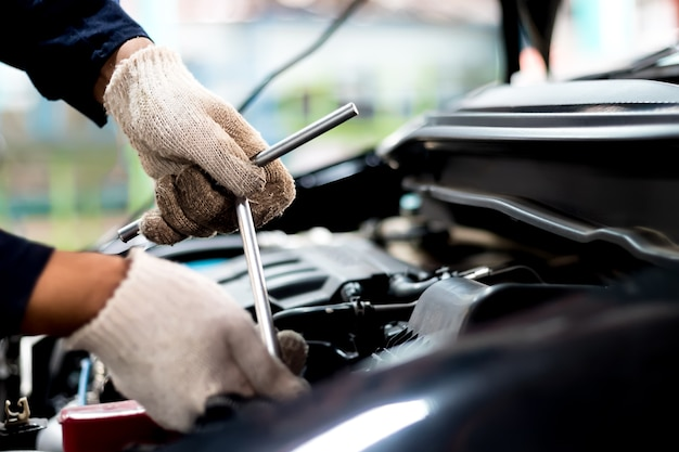 Close up, people are repair a car use a wrench and a screwdriver to work.