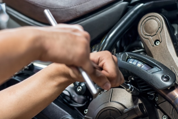 Close up,people are repairing a motorcycle use a wrench and a screwdriver to work.