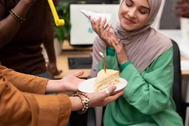 Закройте людей, празднующих коллегу с тортом