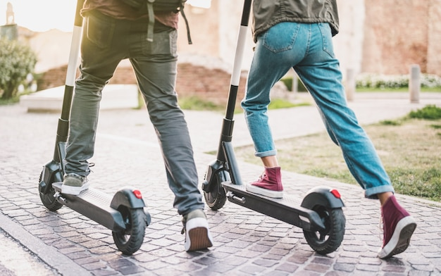 Close up of people couple using electric scooter in city park