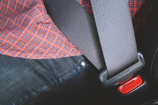 Close up of people hand fastening seat safety belt in car for safety before driving on the road