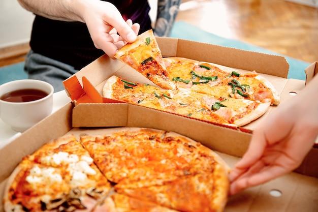 Закройте руки людей, берущих кусочки пиццы из коробки для пиццы. друзья вместе едят пиццу. доставка еды. итальянская кухня