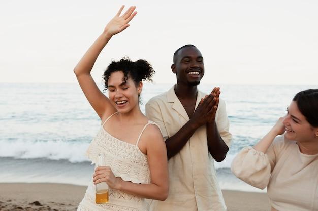해변에서 즐거운 시간을 보내는 사람들을 닫습니다