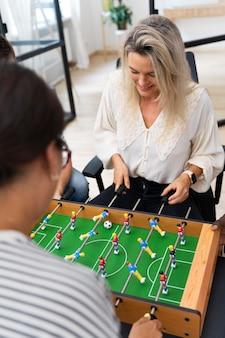 Primo piano sulle persone che si divertono mentre giocano a calcio balilla