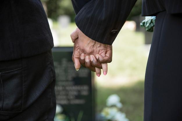 Chiudere le persone che si tengono per mano vicino alla tomba della persona amata