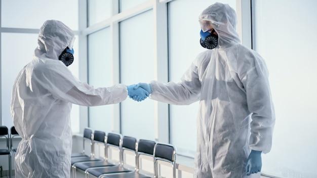 Крупный план. люди в защитных костюмах пожимают друг другу руки. концепция охраны здоровья.
