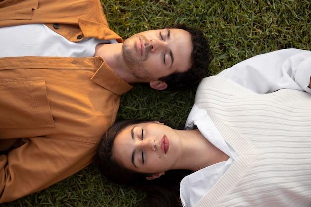 Закройте людей, лежащих на траве