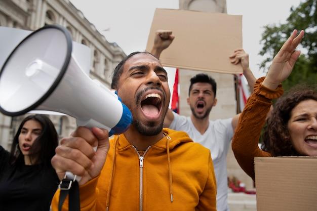 メガホンで抗議する人々をクローズアップ