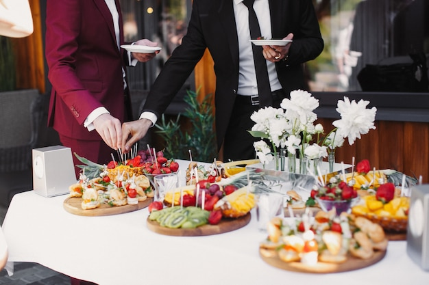 Close up of people serving themselves the fruits in buffet of restaurant