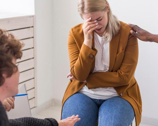 Persone in primo piano che sostengono donna triste