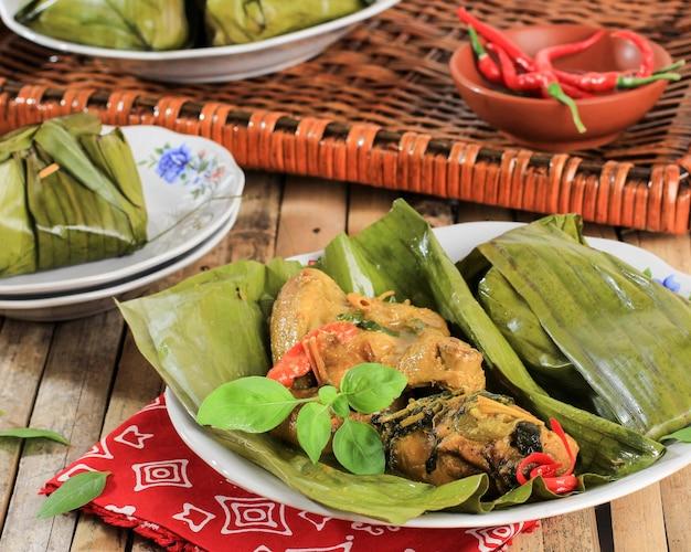 Close up пепес аям паис хаям - индонезийский тушеный цыпленок с карри по традиционному рецепту