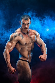Close up on perfect abs. strong bodybuilder with six pack.strong bodybuilder man with perfect abs, shoulders,biceps, triceps and chest, personal fitness trainer flexing his muscles in blue, red smoke