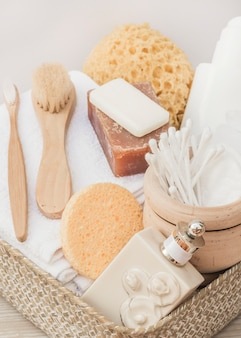 Close-up of perfume bottle; brush; sponge; soap; cotton swab; towel and body scrub in tray