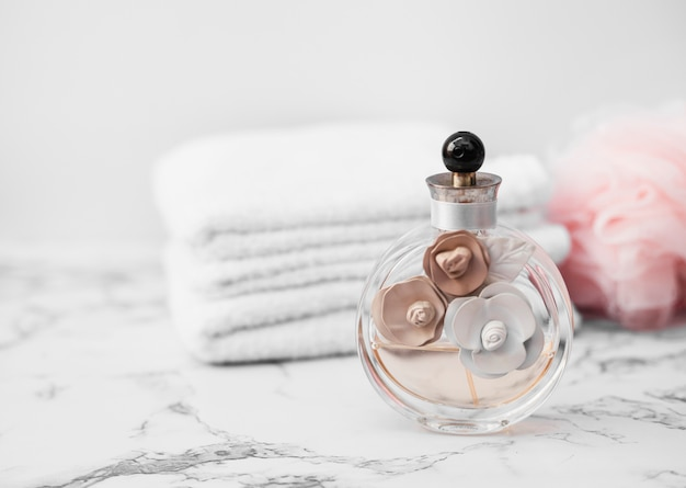 Close-up of perfume bottle in front of towel and sponge on marble surface