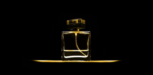 Close-up of perfume bottle isolated on black. panoramic studio photo. fortuna gold of color, 2021 trend.