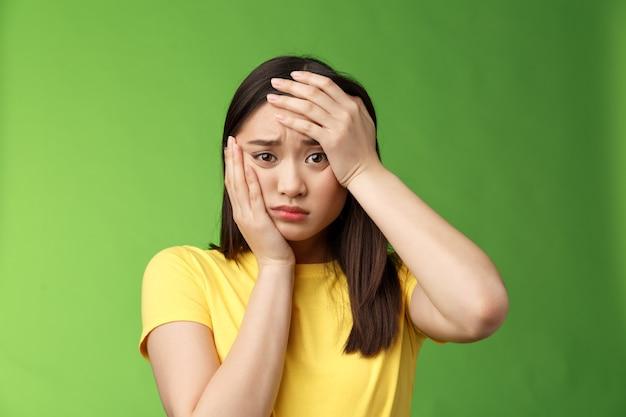 클로즈업된 황폐하고 괴로워하는 귀여운 십대 소녀는 시험 통과를 걱정하고 머리, 얼굴 손바닥, 인상을 찌푸린 얼굴을 찡그린 표정을 하는 화가, 으스스한 끔찍한 상황이 스트레스와 우울을 느낍니다.