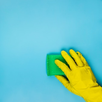 Close-up person cleaning with green sponge
