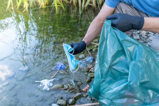 Close up of person collecting mask and gloves from the river. man cleaning river of plastics. environment concept.