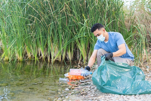 Close up of person collecting plastic from the river. man cleaning river of plastics.