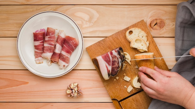 Close-up of a person cutting the bread slice with rolled up bacon on white dish over the wooden table