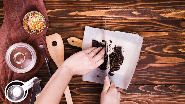 Close-up of a person cutting the chocolate bar with knife on paper over the wooden table