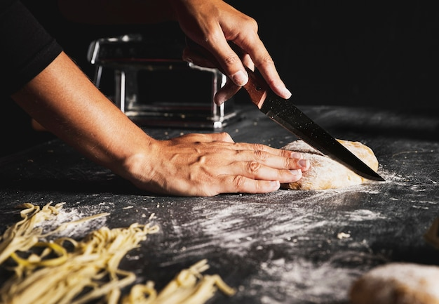Close-up person cutting dough with knife