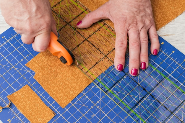 Close-up of a person cutting fabric pieces by rotary cutter on mat using ruler