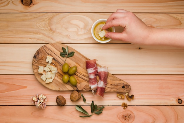 Close-up of a person dipping the bread slice in infused olive with bacon; olive and walnuts on wooden desk