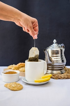 Close-up of a person dipping tea bag in cup
